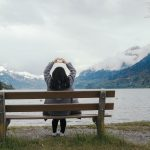 Woman Sitting on Bench at Lake Holding Hands in the Shape of a Heart